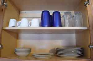 Inside photo of the cupboard showing all of the dishes, glasses and cups we provide