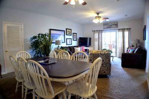 A nice scallop back 6 person dining table, spacious living room with carpeting throughout