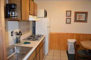 The kitchen is a full service kitchen with a large refrigerator, microwave, rangetop stove and all pots and pans