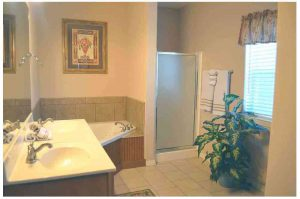 The master bathroom features a corner jacuzzi and a stand up shower as well as a 2 person sink