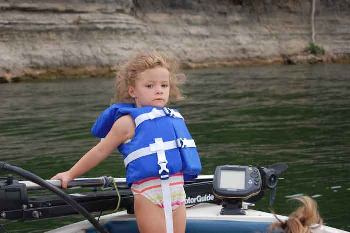 Picture of a little girl wearing a life vest on the front of a boat relaxing